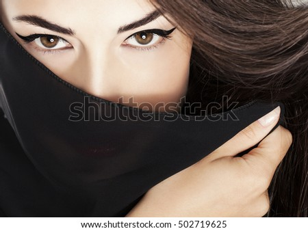 beautiful woman with black scarf over her face, studio closeup