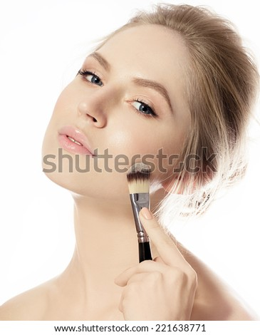 Beautiful woman with blond hair and perfect skin applying foundation on her face - stock photo