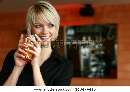 Beautiful woman with blond hair holding a drink smiling sideways. - stock photo