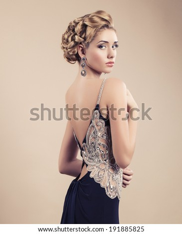 beautiful woman with blond hair in luxury elegant dress posing at studio - stock photo
