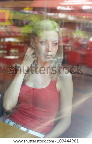beautiful woman with blond hair near a window. view from outside.