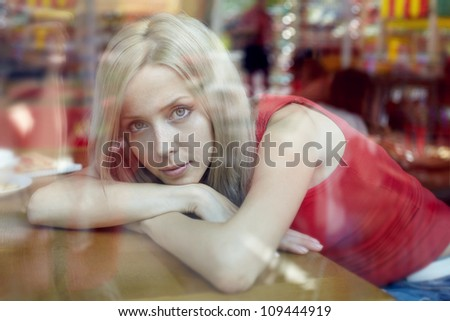 beautiful woman with blond hair near a window. view from outside. - stock photo
