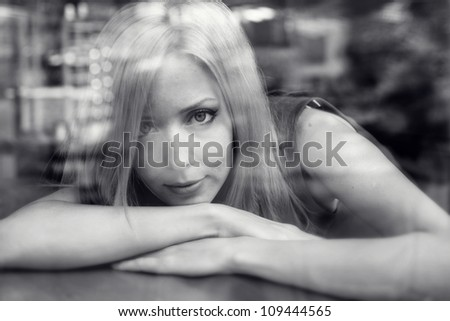 beautiful woman with blond hair near a window. view from outside. black and white