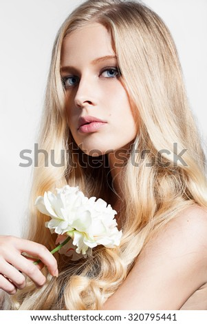 Beautiful woman with blond hair with flower - stock photo