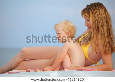 beautiful woman with blond  little baby girl lying on beach, looking afar - stock photo