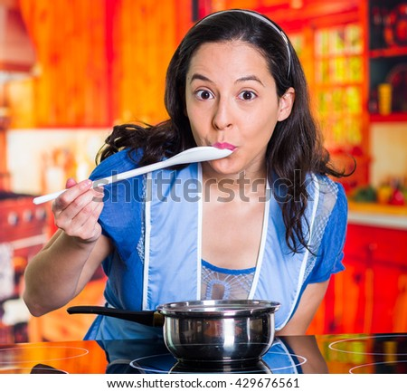 Beautiful woman with blue apron testing the flavor of the preparation on a pot - stock photo