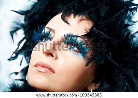 Beautiful woman with blue feather lashes. Fashion photo - stock photo