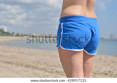 Beautiful woman with blue shorts, enjoying looking view of beach ocean on summer day. Beach vacation. - stock photo