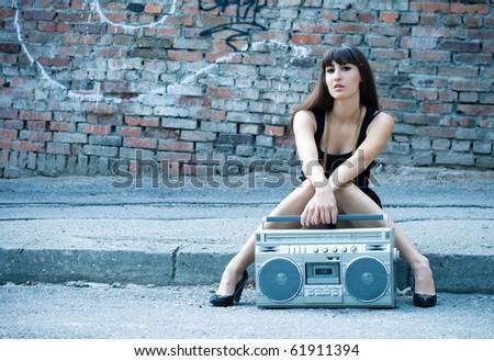 Beautiful woman with boom box on the street - stock photo