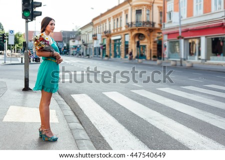 Beautiful woman with bouquet of flowers waiting for green light in front of pedestrian crossing - stock photo