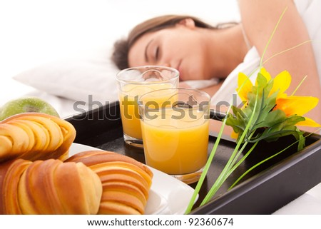 Beautiful woman with breakfast in bed - stock photo