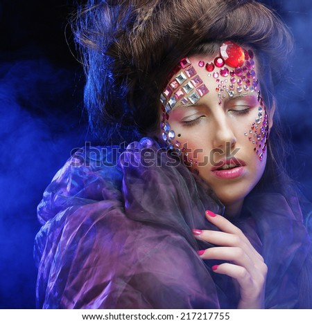Beautiful woman with bright creative make up in blue smoke - stock photo