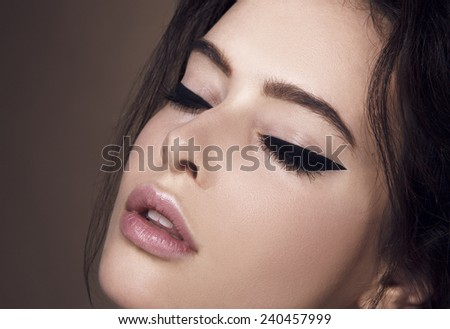 Beautiful woman with bright make up eye with sexy black liner makeup. Fashion big arrow shape on woman's eyelid. Chic evening make-up - stock photo
