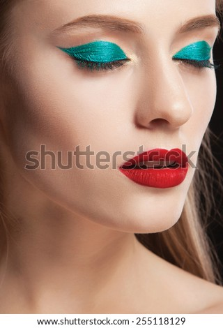 Beautiful woman with bright make up eye with sexy green liner makeup,matt red lips. Fashion big arrow shape on woman's eyelid. Chic evening make-up - stock photo