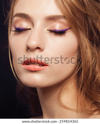 Beautiful woman with bright make up eye with sexy purple sparky gloss liner makeup. Fashion big arrow shape on woman's eyelid. Chic evening make-up, healthy face,curly hair - stock photo