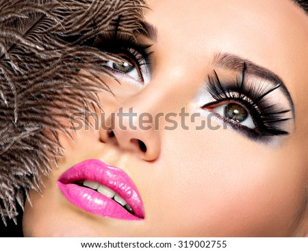 Beautiful woman with bright professional make-up with feathers near the face. - stock photo