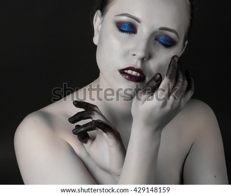 Beautiful woman with bright smoky eyes make-up, black and white skin and finger in the paint on a dark background