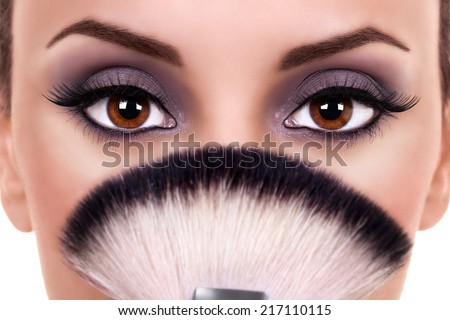 Beautiful woman with brown eyes wearing eye shadow and holding makeup brush
