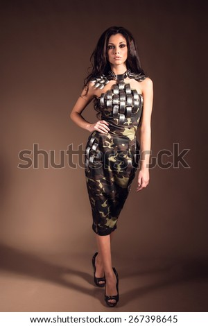 Beautiful woman with brown hair in fashion military clothing. Studio shot - stock photo