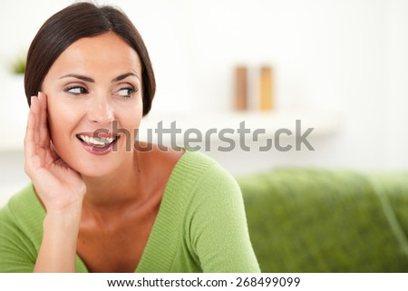 Beautiful woman with brown hair smiling and looking away while putting hand on face - copy space - stock photo