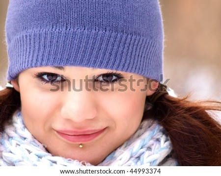 Beautiful woman with brown hair, wearing purple hat and a matching scarf at winter