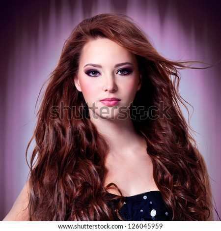 Beautiful woman with brown long curly  hairs over stylized background