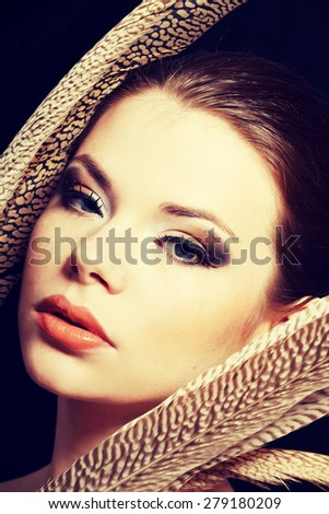 Beautiful woman with brown professional make-up with feathers - stock photo