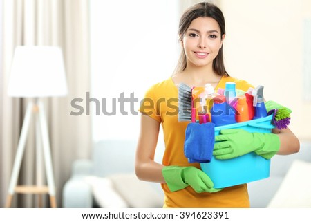 Beautiful woman with bucket of cleaning supplies - stock photo