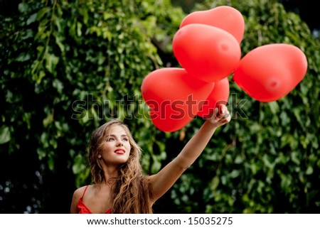 Beautiful woman with bunch of hearts outdoors - stock photo