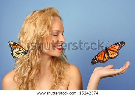 Beautiful Woman With Butterfly in Her Hand and Hair - stock photo