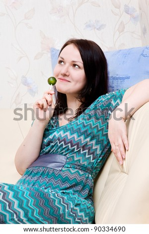 Beautiful woman with candy sitting on the sofa at her home - stock photo