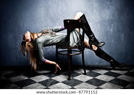 beautiful woman with carnival mask posing on chair, full body shot, indoor shot - stock photo