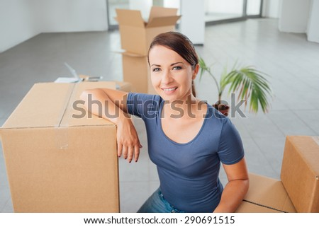 Beautiful woman with carton boxes moving in her new house and smiling at camera - stock photo