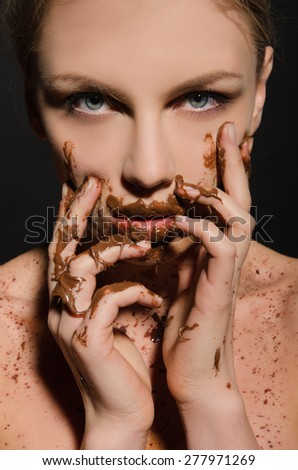beautiful woman with chocolate on her face on dark background - stock photo