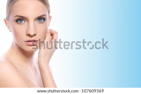 Beautiful woman with clean face over blue background - stock photo