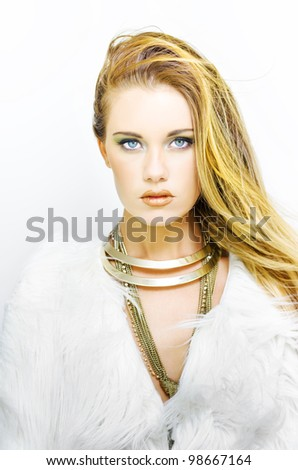 Beautiful woman with clean fresh skin wearing gold necklace and furry coat looking straight at the camera on a white background in a makeup and cosmetics conceptual