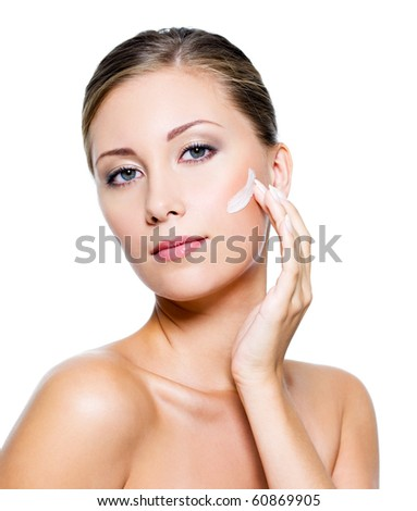 Beautiful woman with clean skin applying cosmetic cream on face - stock photo