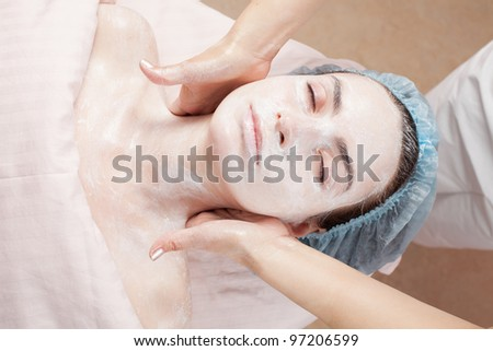 Beautiful woman with clear skin getting beauty treatment of her face at salon. - stock photo