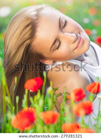 Beautiful woman with closed eyes lying down on poppy flower field, relaxation outdoors on fresh gentle floral meadow, enjoying spring nature