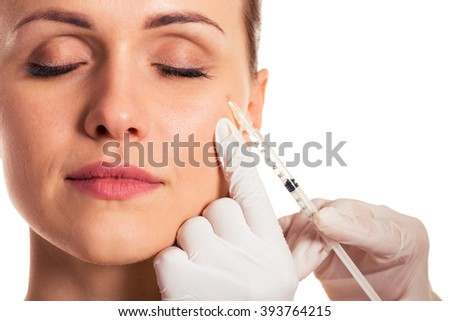 Beautiful woman with closed eyes, surgeon in medical gloves is making an injection in face, isolated on a white background, close-up