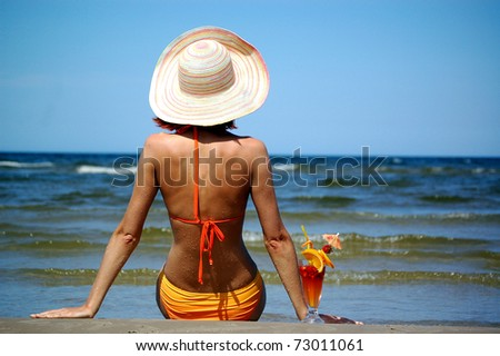 Beautiful woman with cocktail on the beach - stock photo