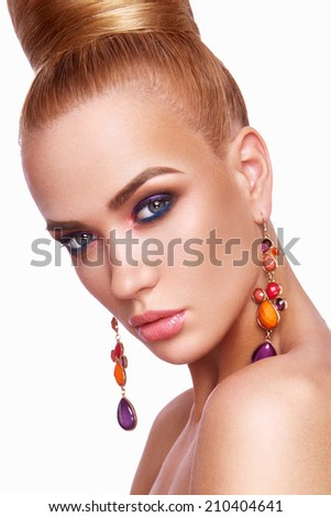 Beautiful woman with colored makeup and earrings. - stock photo