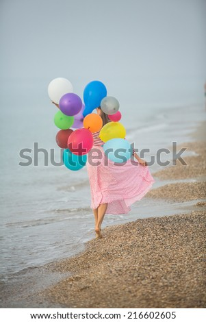 Beautiful woman with colorful balloons on seaside in early foggy morning - stock photo