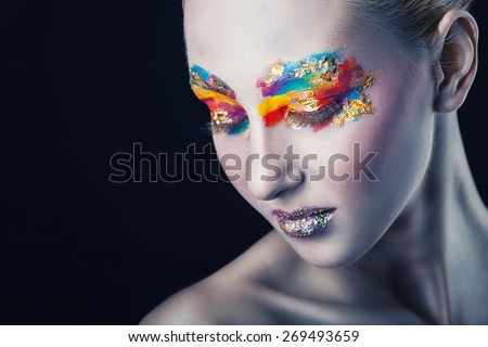 Beautiful woman with colorful makeup on black background. Focus on the eye - stock photo