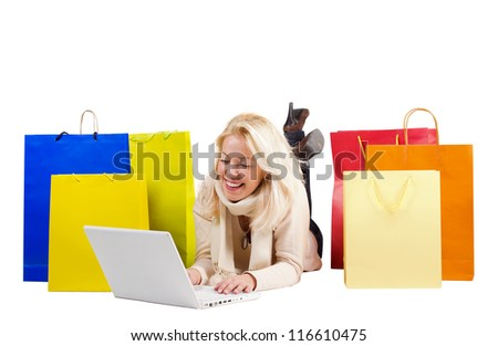 Beautiful woman with colorful shopping bags and a laptop - stock photo