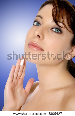 Beautiful woman with cream on tip of her fingers, applying it to her face. - stock photo