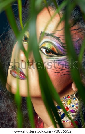 Beautiful woman with creative tiger style make-up hiding in the jungle, closeup shot - stock photo