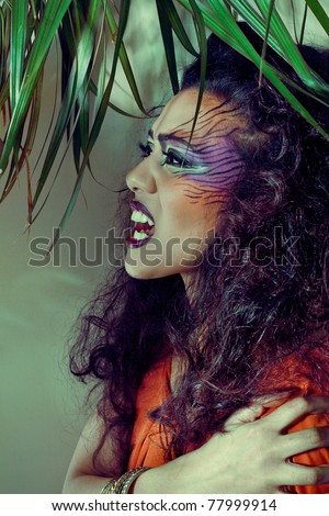 Beautiful woman with creative tiger style make-up in jungle, closeup shot - stock photo