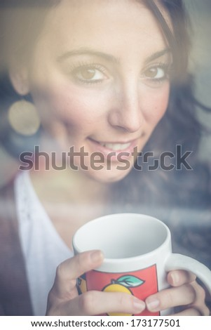 beautiful woman with cup facing through window at home