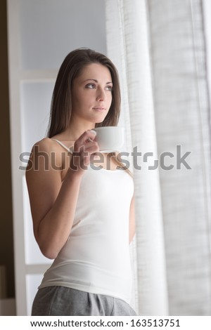 Beautiful woman with cup of coffee looking out of window.  - stock photo